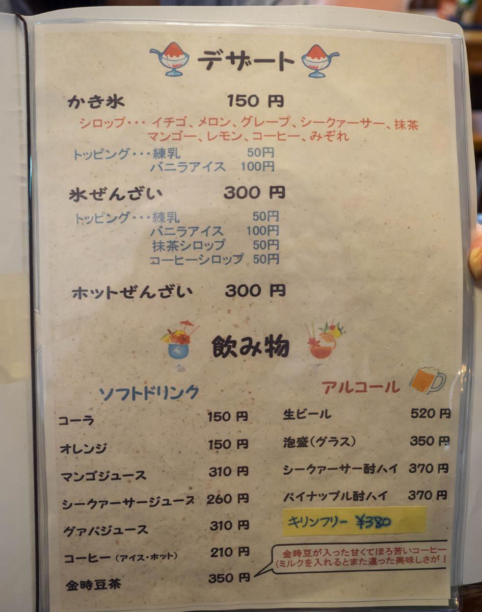 恩納そばのメニュー3:デザート:かき氷(シロップ・・いちご、メロン、グレープ、シークワァーサー、抹茶、マンゴー、レモン、コーヒー、みぞれ) 150円、かき氷トッピング(練乳 50円、バニラアイス 100円)、氷ぜんざい 300円、氷ぜんざいトッピング(練乳 50円、バニラアイス 100円、抹茶シロップ 50円、コーヒーシロップ 50円)、ホットぜんざい 300円:ソフトドリンク:コーラ 150円、オレンジ 150円、マンゴージュース 310円、シークワァーサージュース 260円、グァバジュース 310円、コーヒー(アイス・ホット) 210円、金時豆茶(金時豆が入った甘くてほろ苦いコーヒー) 350円:アルコール:生ビール 520円、泡盛グラス 350円、シークワァーサー酎ハイ 370円、パイナップル酎ハイ 370円、キリンフリー 380円