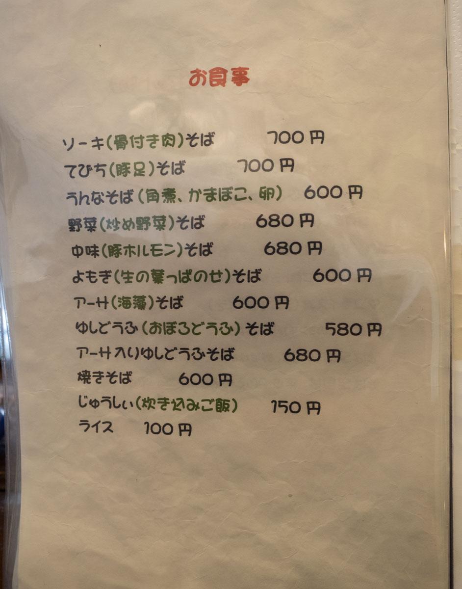 恩納そばのメニュー1:ソーキそば 700円、てびちそば 700円、うんなそば(角煮、かまぼこ、卵) 600円、野菜(炒め野菜)そば 680円、中味(豚ホルモン)そば 680円、よもぎ(生の葉っぱのせ)そば 600円、アーサ(海藻)そば 600円、ゆしどうふ(おぼろどうふ)そば 580円、アーサ入りゆしどうふそば 680円、じゅうしぃ(炊き込みご飯) 150円、ライス 100円